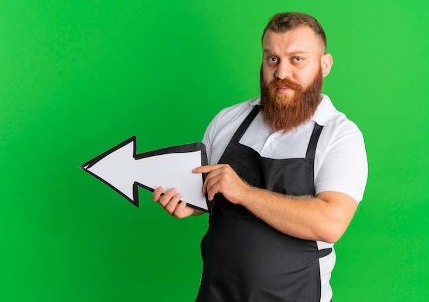 Professional bearded barber man in apron holding big arrow sign pointing to the left looking confident standing over green wall