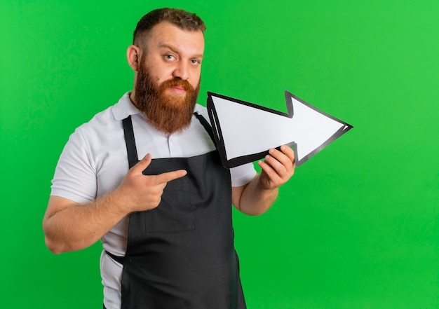 Professional bearded barber man in apron holding big arrow sign pointing to the right pointing with finger to it standing over green wall