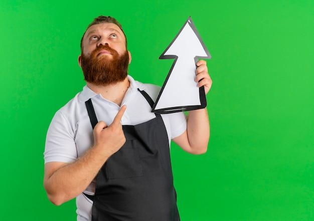 Barbiere barbuto professionista uomo in grembiule che tiene grande segno di freccia rivolta verso l'alto in piedi sopra la parete verde