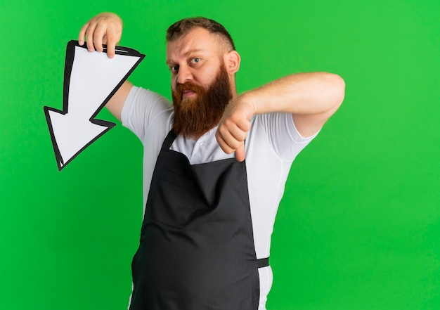 Professional bearded barber man in apron holding big arrow sign pointing with it and finger down standing over green wall