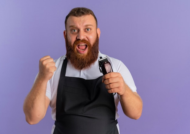 Professional bearded barber man in apron holding hair cutting machine happy and excited clenching fist rejoicing his success standing over purple wall