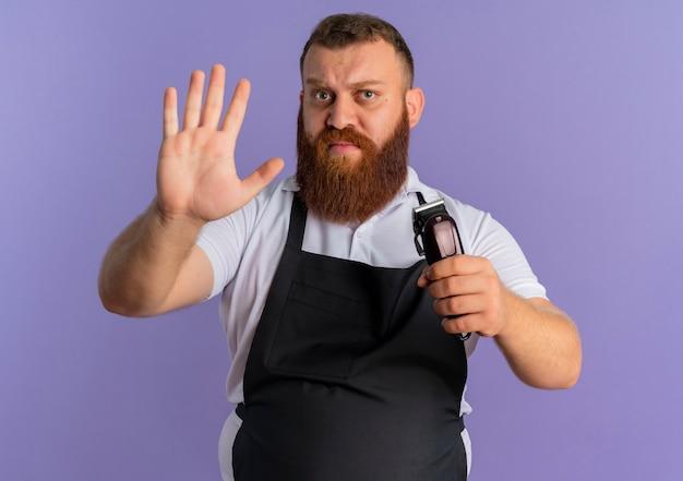 Uomo barbuto professionale del barbiere in grembiule che tiene macchina per il taglio dei capelli facendo il segnale di stop con la mano aperta con la faccia seria in piedi sopra la parete viola