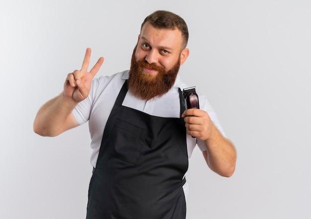 Uomo barbuto professionale del barbiere in grembiule che tiene la macchina per il taglio dei capelli che mostra il segno di vittoria o il numero due sorridente in piedi sopra il muro bianco