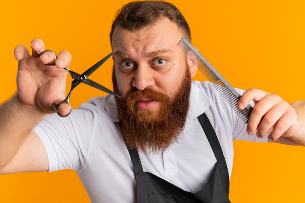 Professional bearded barber man in apron holding scissors and hairbrush going to cut standing over orange wall