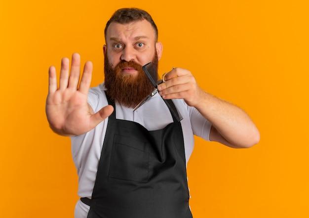 Uomo barbuto professionale del barbiere in grembiule che tiene le forbici e la spazzola per capelli facendo il fanale di arresto con la mano con l'espressione di paura in piedi sopra la parete arancione