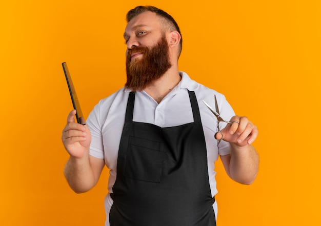Uomo barbuto professionale del barbiere in grembiule che tiene le forbici e la spazzola per capelli con il sorriso sul viso in piedi sopra la parete arancione