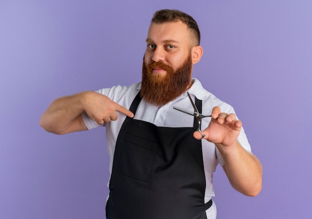 Professional bearded barber man in apron holding scissors pointing with finger to it looking confident standing over purple wall