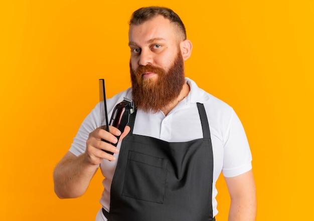 Uomo barbuto professionale del barbiere in grembiule che tiene macchina da barba e spazzola per capelli guardando fiducioso in piedi sopra la parete arancione