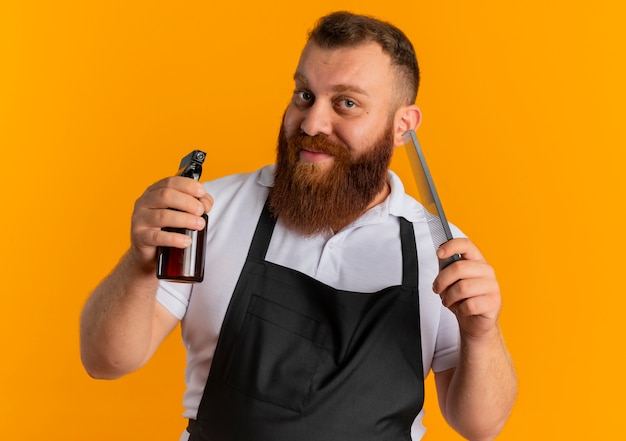 Professional bearded barber man in apron holding spray and hairbrush with smile on face standing over orange wall
