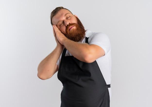 Barbiere barbuto professionista uomo in grembiule guardando stanco tenendo le palme insieme appoggiando la testa sui palmi con gli occhi chiusi in piedi sopra il muro bianco