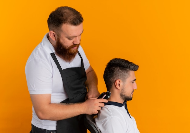 Professional bearded barber man in apron making haircut with shaving machine to a young man standing over orange wall