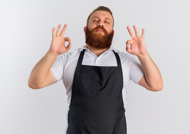 Uomo barbuto professionista barbiere in grembiule rilassante con gli occhi chiusi che fa gesto di meditazione con le dita in piedi sopra il muro bianco
