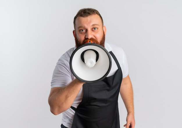 Professional bearded barber man in apron shouting to megaphone standing over white wall