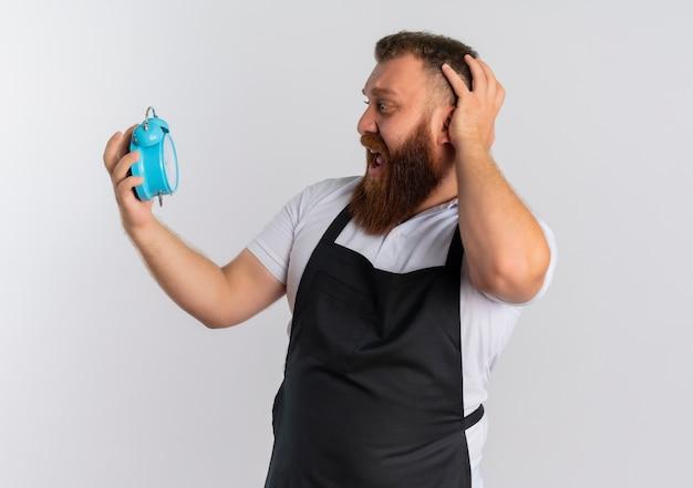 Uomo barbuto professionista del barbiere in grembiule che mostra sveglia guardandolo urlando in preda al panico in piedi sopra il muro bianco