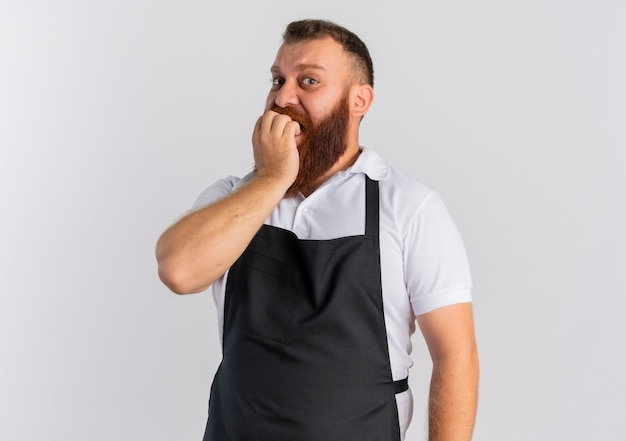 Barbiere barbuto professionista in grembiule unghie mordaci nervose e stressate in piedi sopra il muro bianco