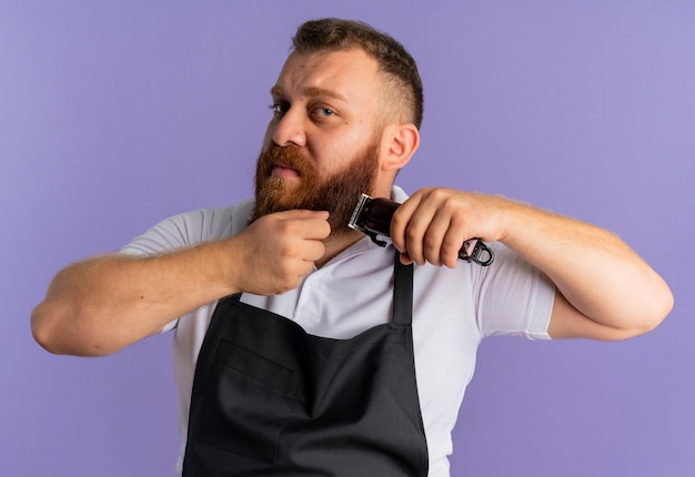 Professional bearded barber man in apron trimming his beard with shaving machine looking confused standing over purple wall