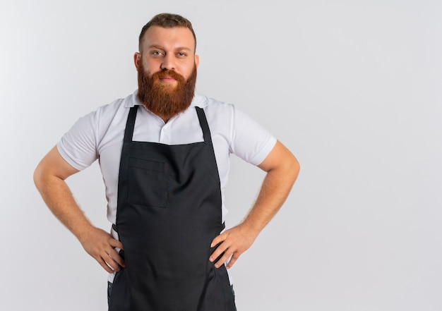 Professional bearded barber man in apron with confident expression standing over white wall