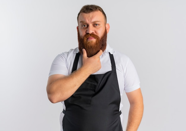 Professional bearded barber man in apron with hand on his chin thinking standing over white wall