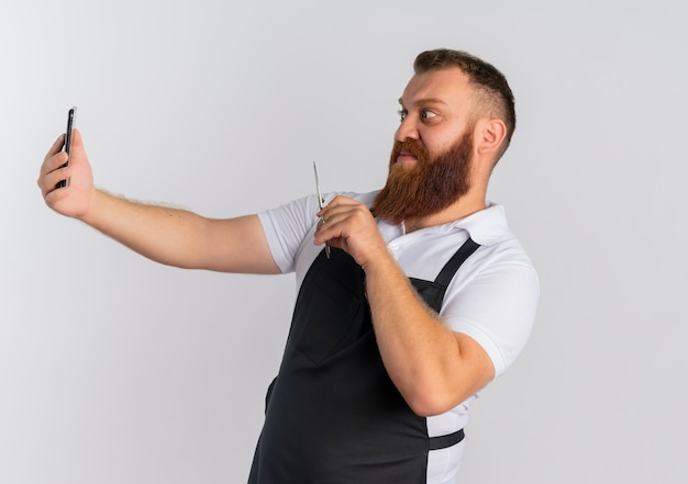 Barbiere barbuto professionista uomo in grembiule con smartphone e forbici, guardando confuso e sconvolto in piedi sopra il muro bianco