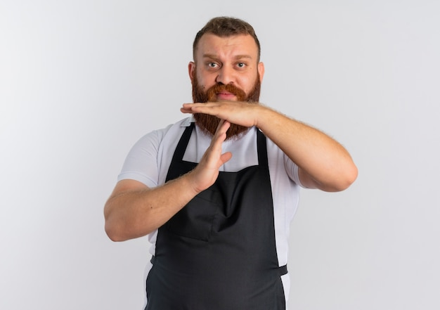 Barbiere barbuto professionista uomo in grembiule preoccupato facendo gesto di time out con le mani in piedi sopra il muro bianco