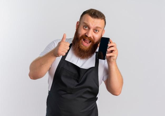Профессиональный бородатый парикмахер в фартуке счастлив и взволнован, разговаривает по мобильному телефону, показывает палец вверх, стоя над белой стеной