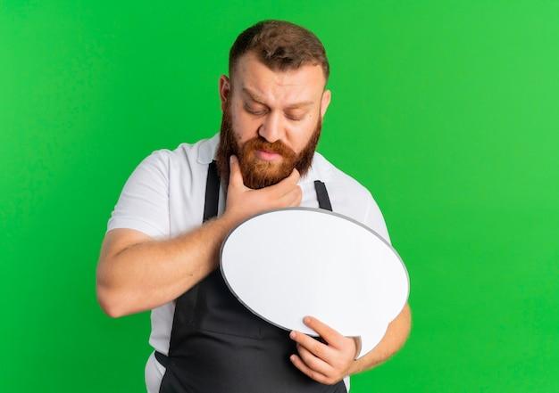Профессиональный бородатый парикмахер в фартуке, держащий пустой речевой пузырь, озадаченный задумчивым выражением лица, стоящий над зеленой стеной