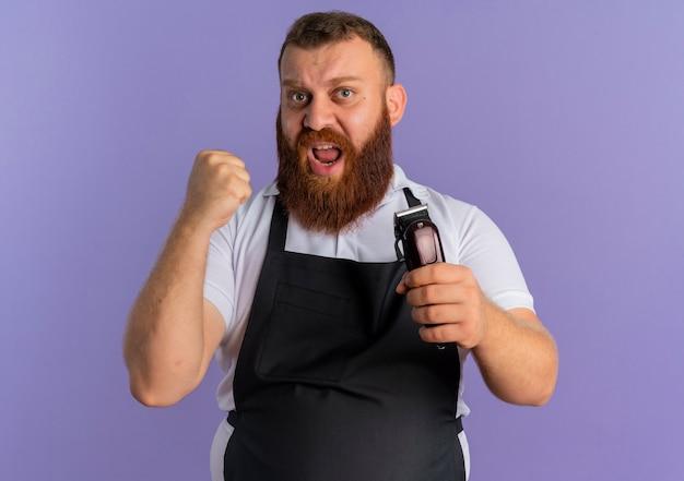 보라색 벽 위에 서있는 공격적인 표정으로 주먹을 떨림 머리 절단 기계를 들고 앞치마에 전문 수염 이발사 남자