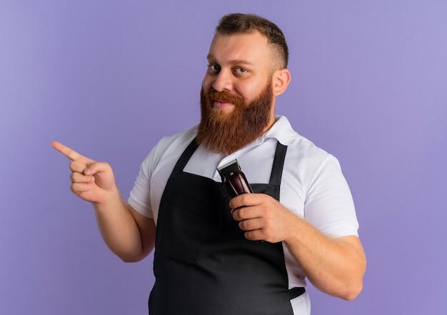 紫色の壁の上に立って微笑んで横に指で指しているヘアカットマシンを保持しているエプロンのプロのひげを生やした理髪店の男