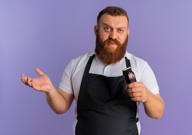 紫色の壁の上に立っている腕で自信を持って表情でヘアカットマシンを保持しているエプロンでプロのひげを生やした理髪店の男