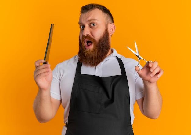 オレンジ色の壁の上に立って驚いたはさみとヘアブラシを保持しているエプロンでプロのひげを生やした床屋の男