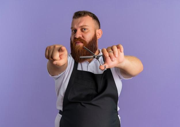 보라색 벽 위에 서 불쾌한 손가락으로 가리키는 가위를 들고 앞치마에 전문 수염 이발사 남자