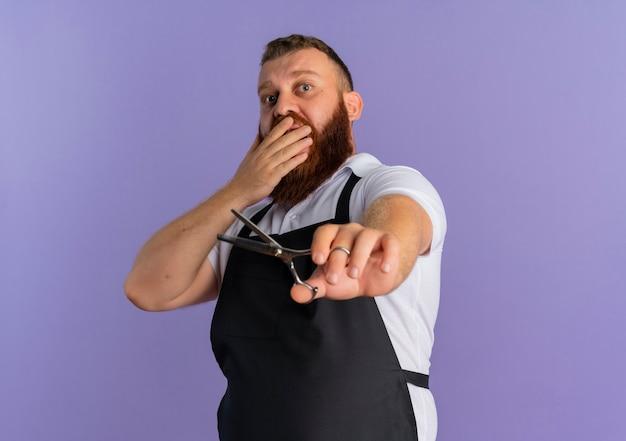 가위를 들고 앞치마에 전문 수염 이발사 남자가 보라색 벽 위에 서있는 손으로 입을 덮고 충격을 받았습니다.