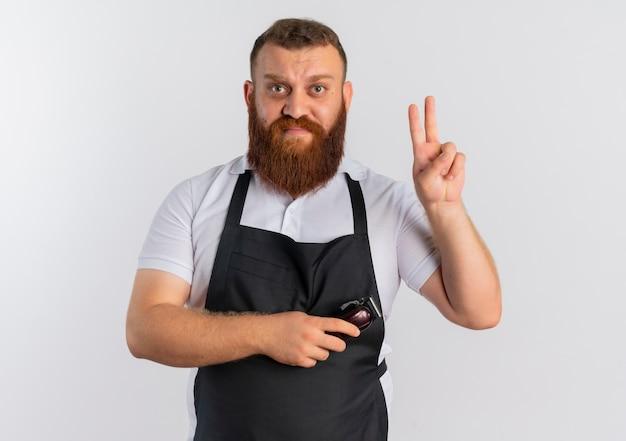 白い壁の上に立って混乱しているように見える指で2番目を示すはさみを持っているエプロンのプロのひげを生やした床屋の男