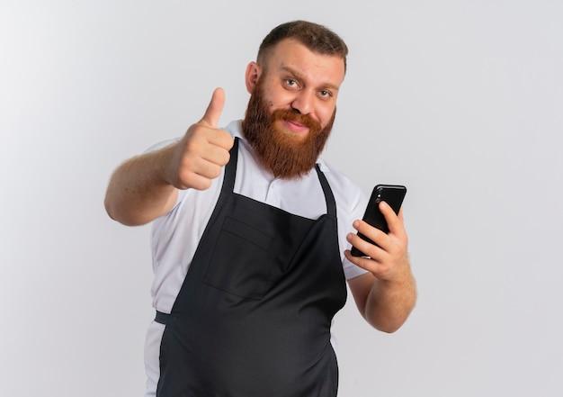 白い壁の上に立って親指を見せて幸せそうな顔の笑顔でスマートフォンを保持しているエプロンでプロのひげを生やした床屋