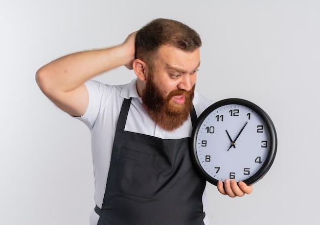 白い壁の上に立って混乱して驚いたように見える壁時計を保持しているエプロンのプロのひげを生やした床屋の男