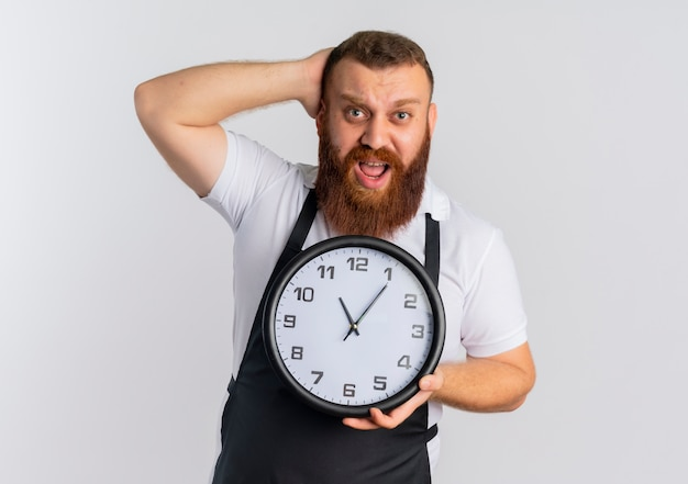 Профессиональный бородатый парикмахер в фартуке держит настенные часы, выглядит смущенным и очень встревоженным, стоя над белой стеной