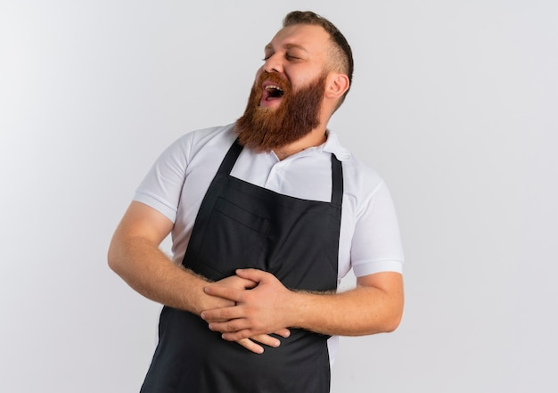 Профессиональный бородатый парикмахер в фартуке смеется, касаясь своего живота, стоящего над белой стеной