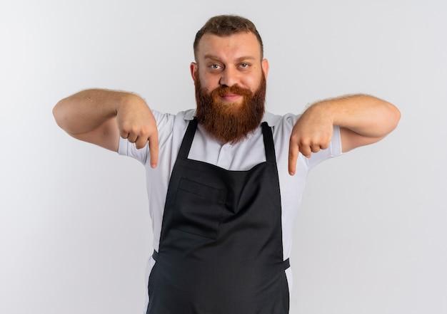 Профессиональный бородатый парикмахер в фартуке выглядит уверенно, указывая пальцами вниз, стоя над белой стеной