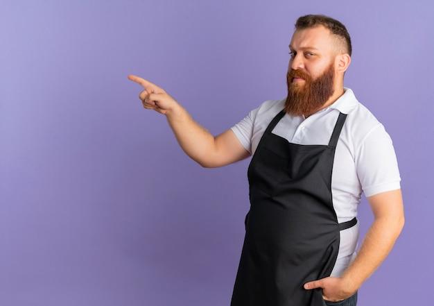 紫色の壁の上に立って左に人差し指で自信を持って指しているエプロンのプロのひげを生やした理髪店の男