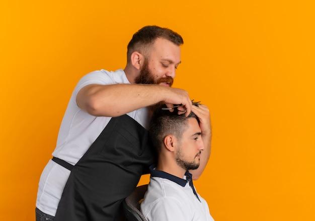 オレンジ色の壁の上に立っている若い男にシェービングマシンで散髪を作るエプロンのプロのひげを生やした理髪店の男
