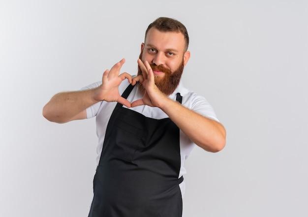 Профессиональный бородатый парикмахер в фартуке делает сердечный жест пальцами на груди, уверенно улыбаясь, стоя над белой стеной