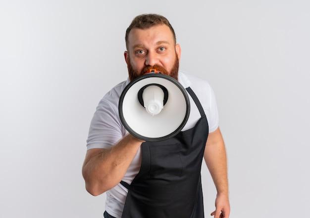 Профессиональный бородатый парикмахер в фартуке кричит в мегафон, стоя над белой стеной