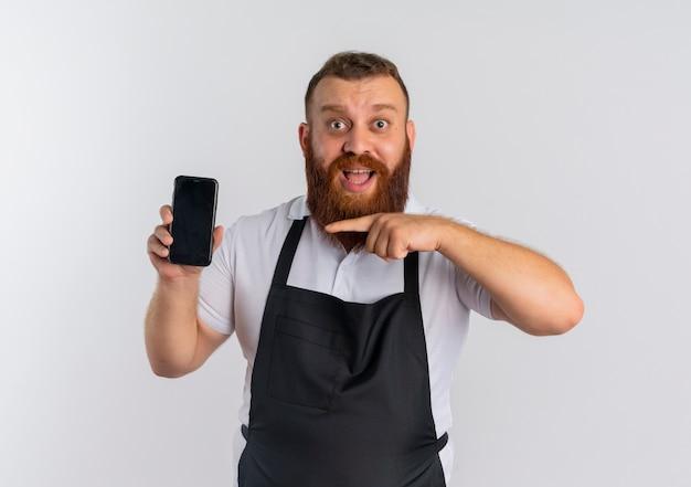エプロンでプロのひげを生やした理髪店の男は、白い壁の上に立って幸せで興奮して笑ってスマートフォンを指で指している