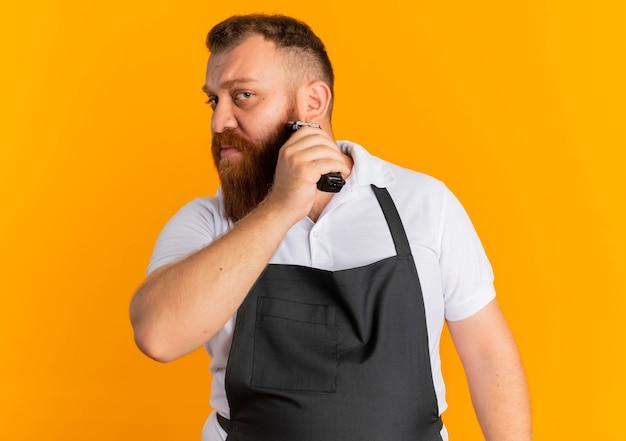 オレンジ色の壁の上に立っているシェービングマシンで彼のひげをトリミングするエプロンのプロのひげを生やした理髪店の男