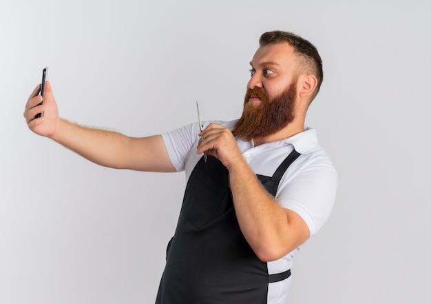 Профессиональный бородатый парикмахер в фартуке со смартфоном и ножницами, смущенный и расстроенный, стоит над белой стеной