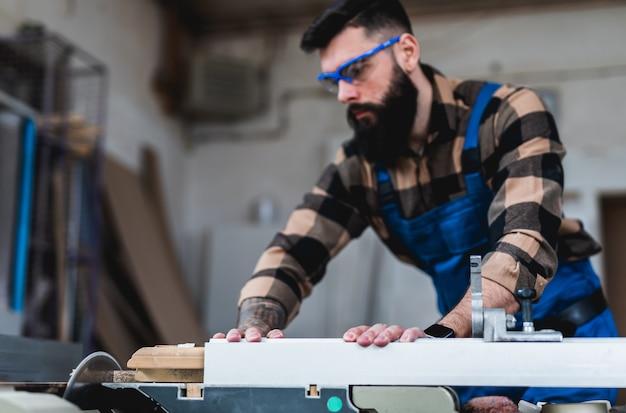 Профессиональный бородатый плотник, работающий в своей мастерской, занимается деревообработкой и мастерством.