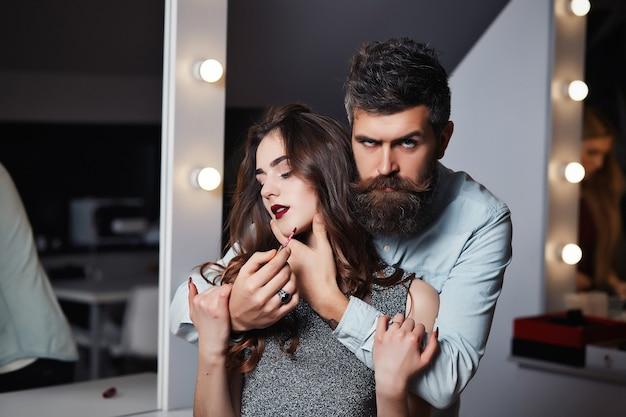 プロのひげを生やしたかわいい男性のメイクアップアーティストは、美容院でブルネットの女の子にリップグロスで唇をペイントします