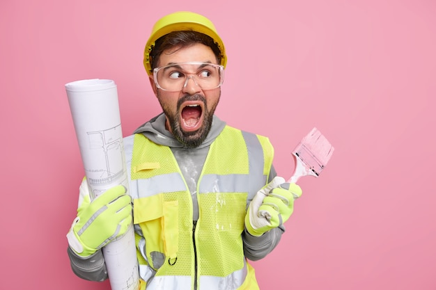 Professional bearded male construction worker souts loudly keeps mouth opened wears safety glasses protective helmet and uniform