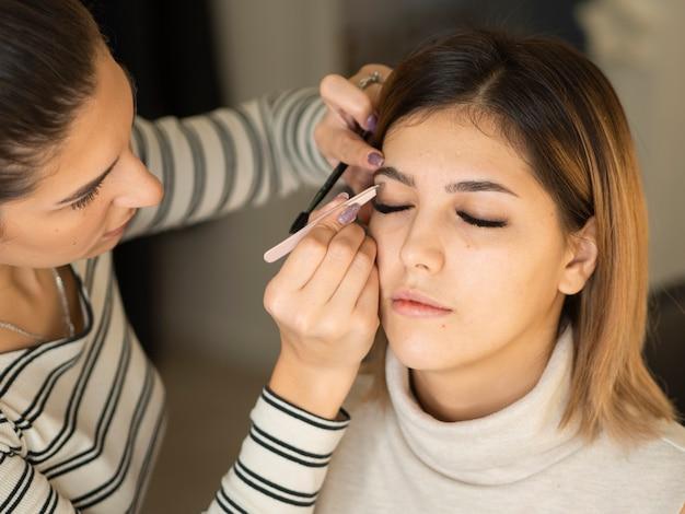 プロの美容師がビューティーサロンのインテリアで眉の矯正を行います