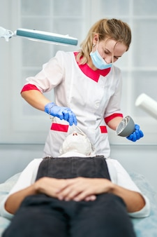 Professional beautician is applying healthy cream on female facial skin with concentration